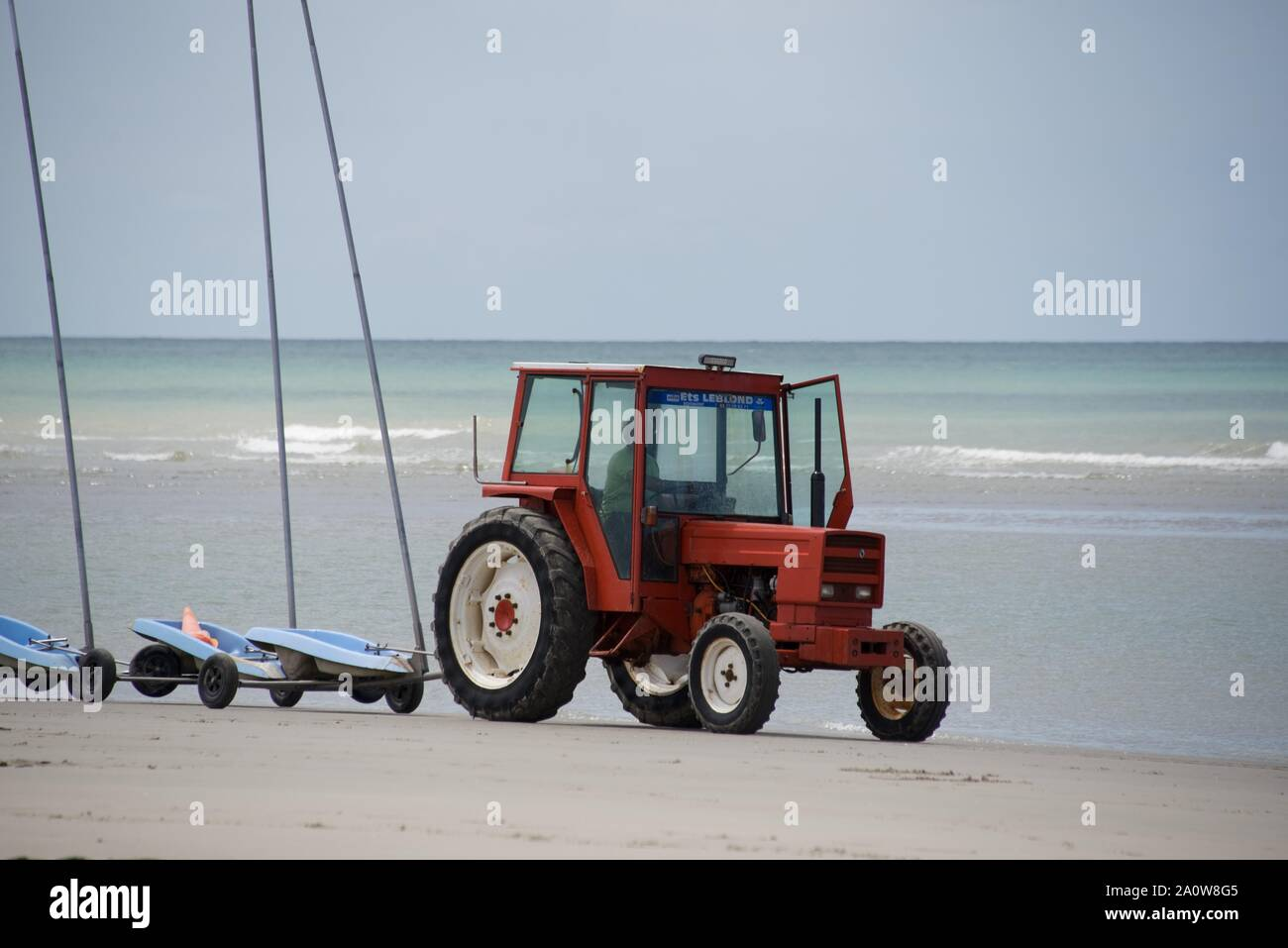 A tractor pulling 9 linked sand yachts, without sails, on to the beach in preparation for a competition Stock Photo