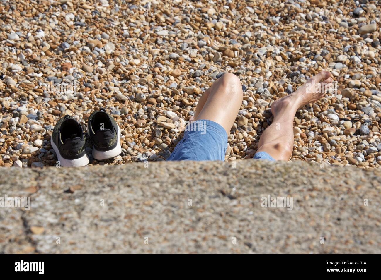 With footwear removed a young man relaxes on a pebble beach in the summer sun Stock Photo