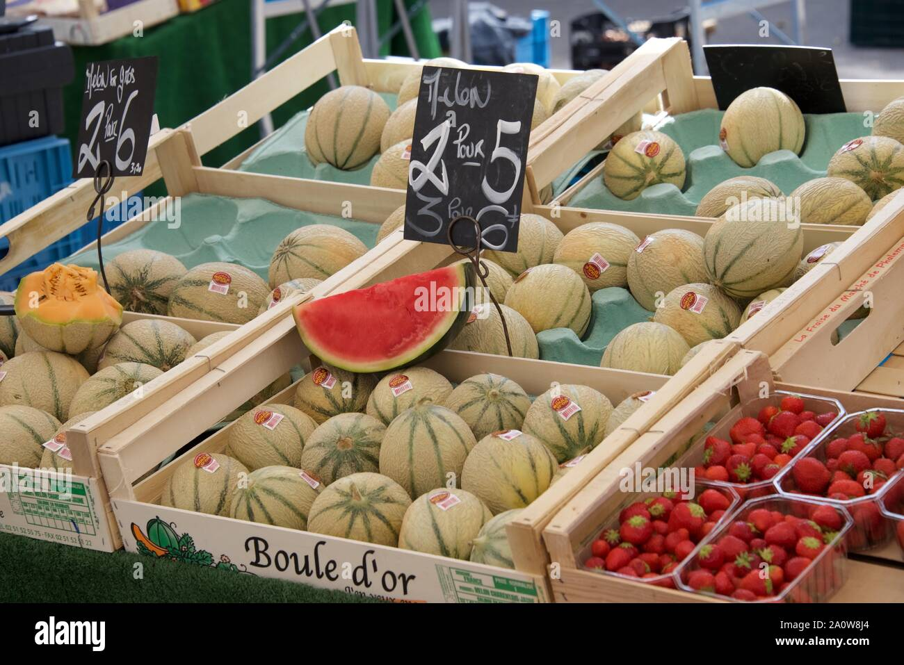 French market stall: Charentais melons and strawberries displayed on a French market stall Stock Photo