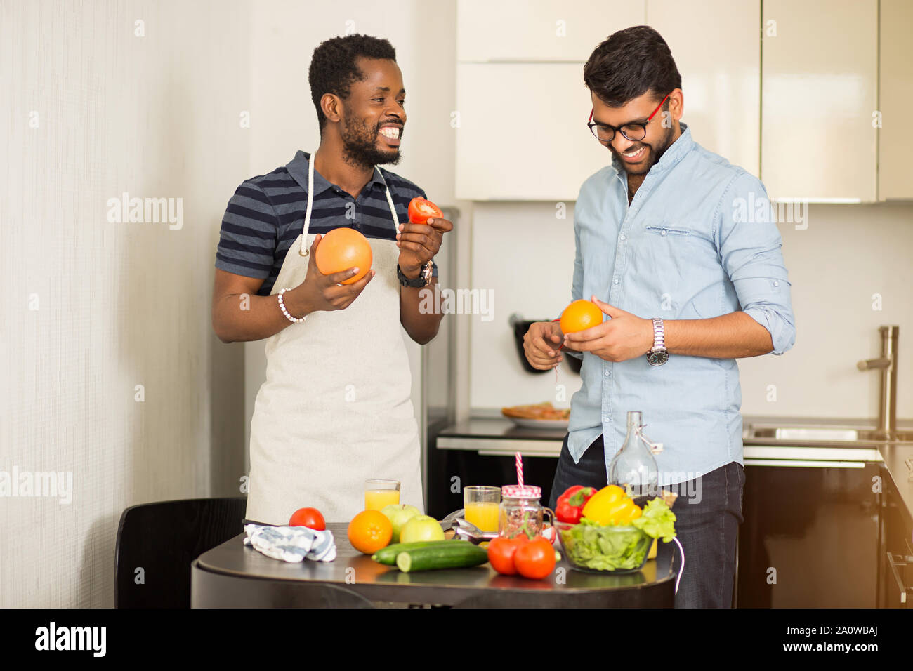 Two male students in casual clothes going to cooking smoothie standing in kitchen of hostel, holding grapefruit, orange, apple, tomato in hands, cheer Stock Photo