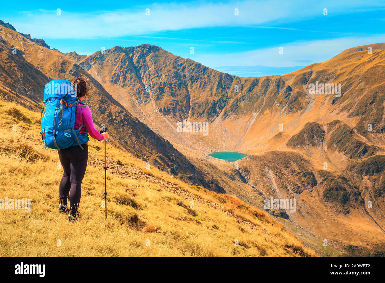 Traveller active hiker woman with colorful backpack enjoying the view from the hills, Fagaras mountains, hiking and travel concept, Carpathians, Roman Stock Photo