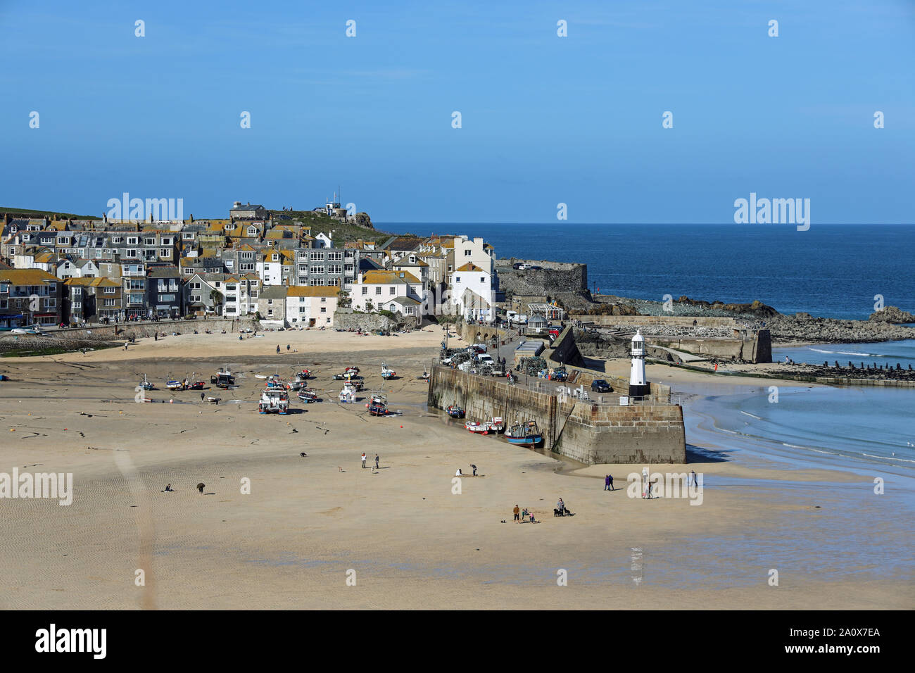Visitors and residents walk along the beach at St Ives when the tide is out Stock Photo