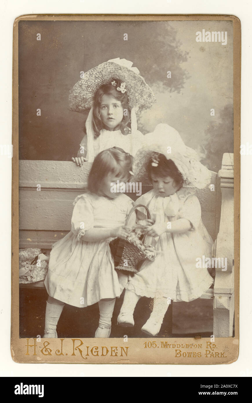 Original antique Edwardian cabinet card, charming studio portrait of three pretty young siblings, sisters, in summer clothes, wearing large straw hats and white smocks, Bowes Park, London, U.K. circa 1904. Stock Photo