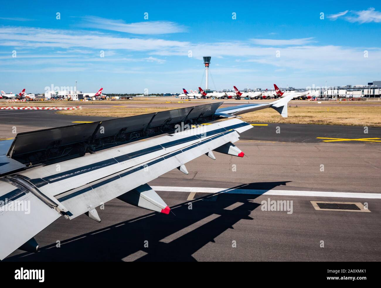 View from plane window over wing landing on airport runway with Virgin Atlantic aeroplanes, London, England, UK Stock Photo