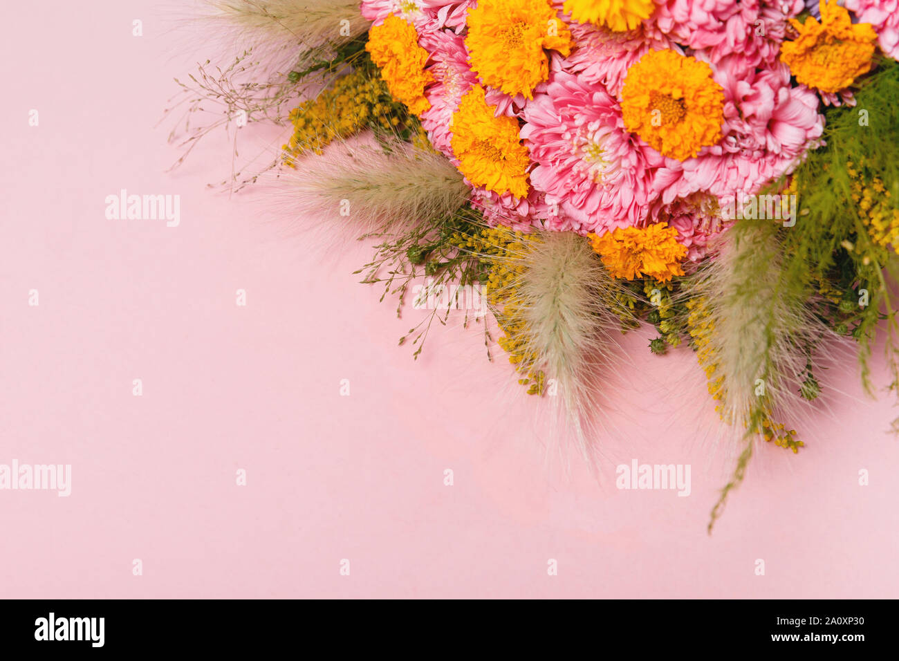 Bouquet Of Autumn Flowers Pink And Yellow Asters And Autumn Leaves And Herbs On Pastel Pink Background Stock Photo Alamy
