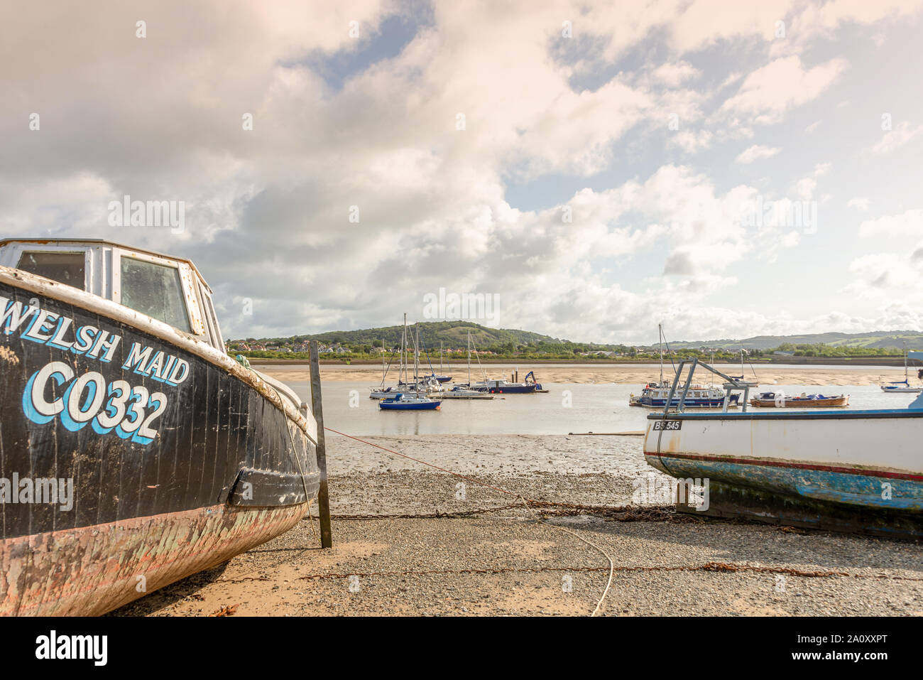 St George's Channel at Conwy.  Two boats are aground on the sand and others are afloat in the channel. Hills are  in the distance. Stock Photo