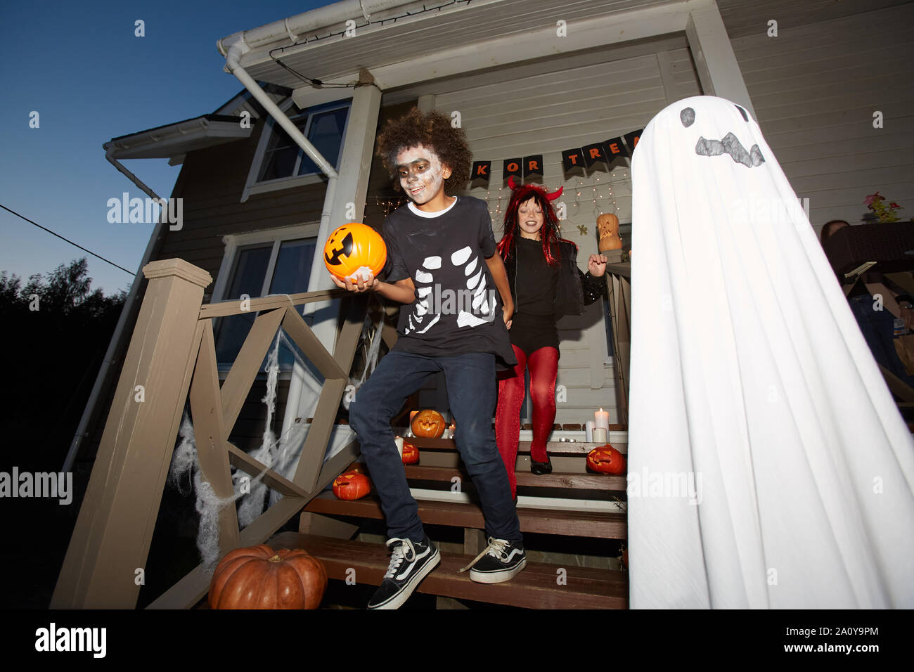 Low angle portrait of happy children leaving house trick or treating on Halloween, focus on smiling African-American boy in foreground, shot with flash Stock Photo