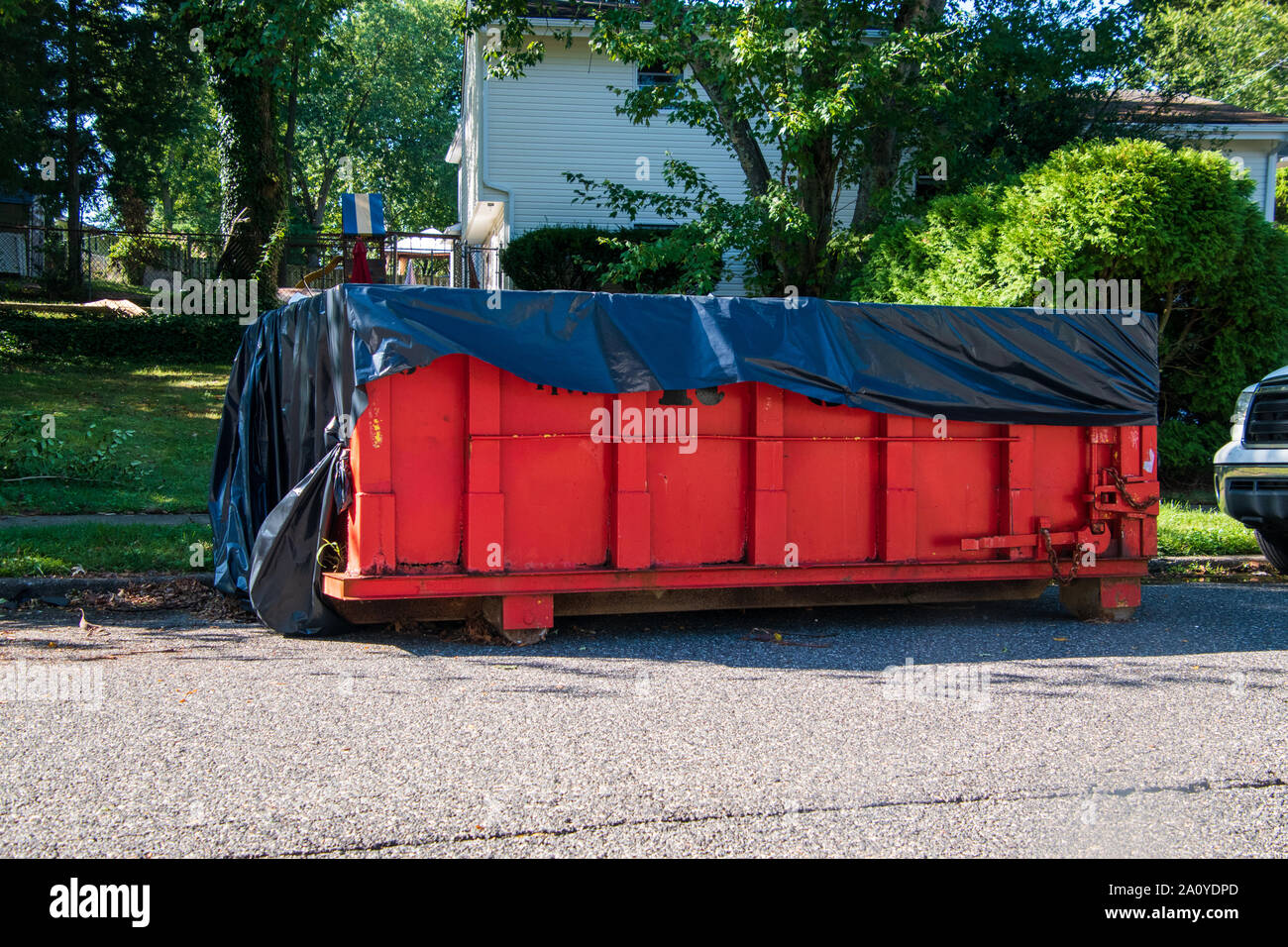 Red dumpster with black plastic liner on a asphalt street near the side of a house with trees in the background Stock Photo