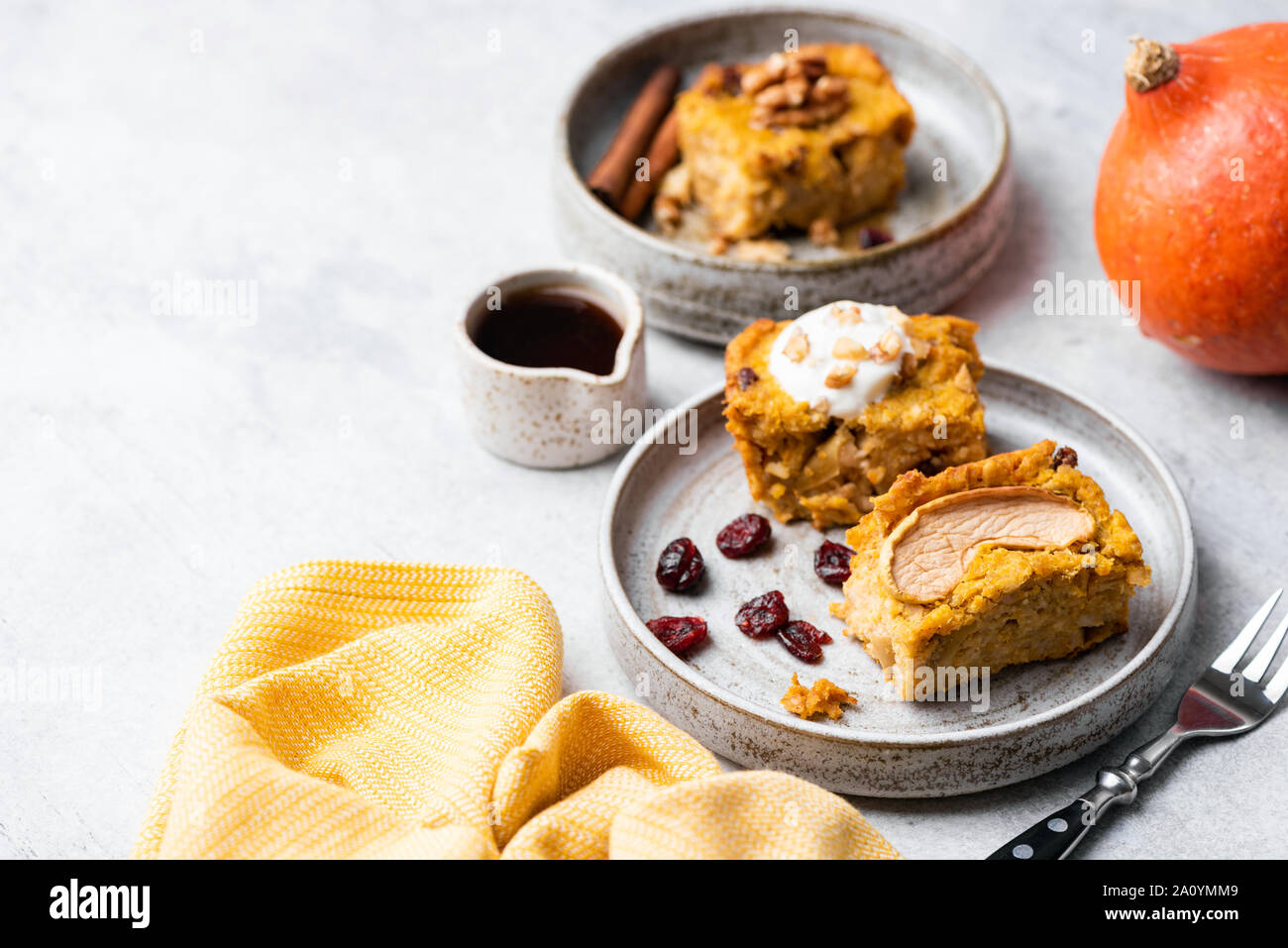 Pumpkin cake square with walnuts, dried cranberry and yogurt on plate. Healthy american pumpkin pie Stock Photo