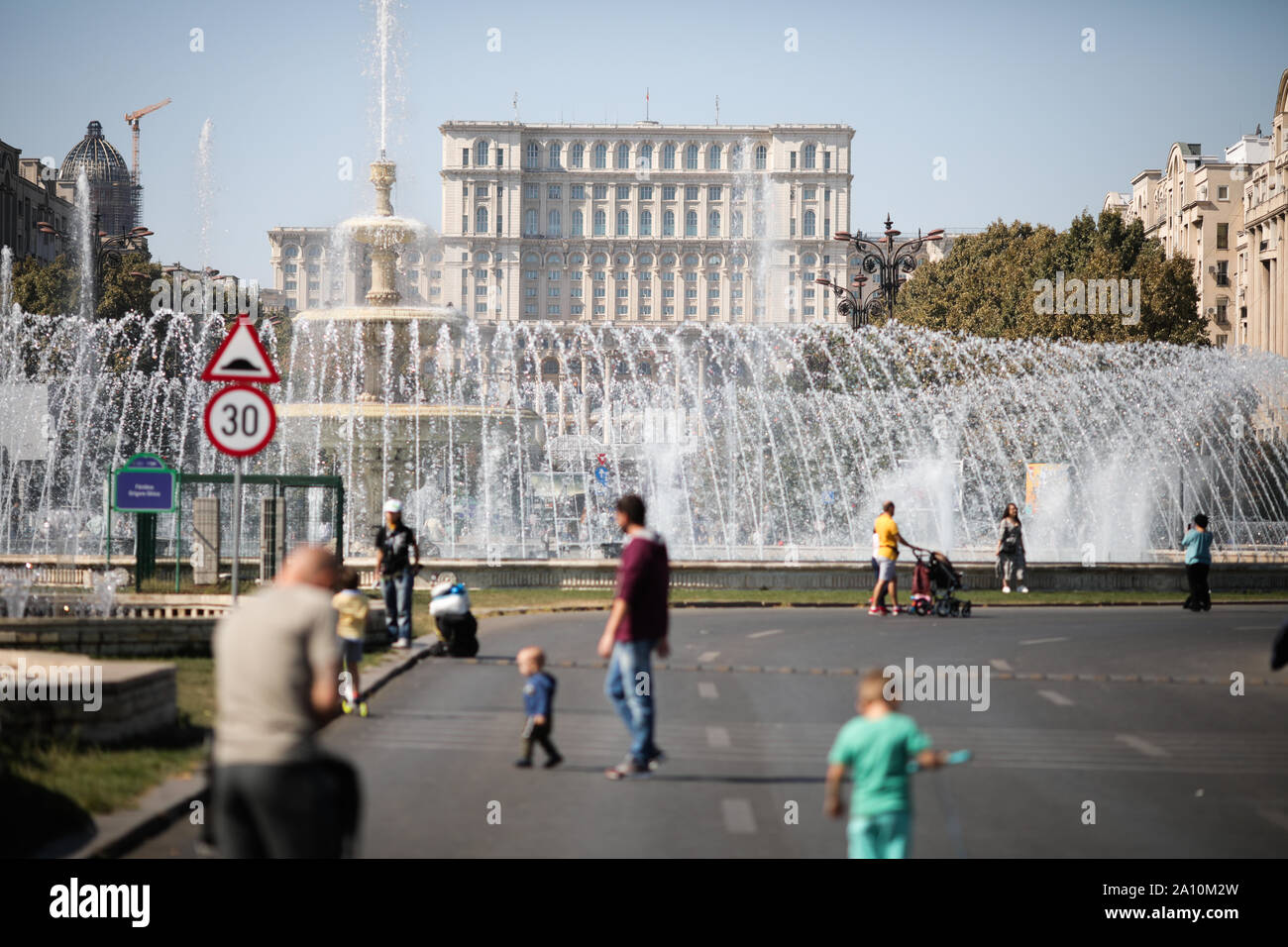 Bucharest, Romania - September 22, 2019: People walk on an empty boulevard with the Palace of Parliament on the background in downtown Bucharest. Stock Photo