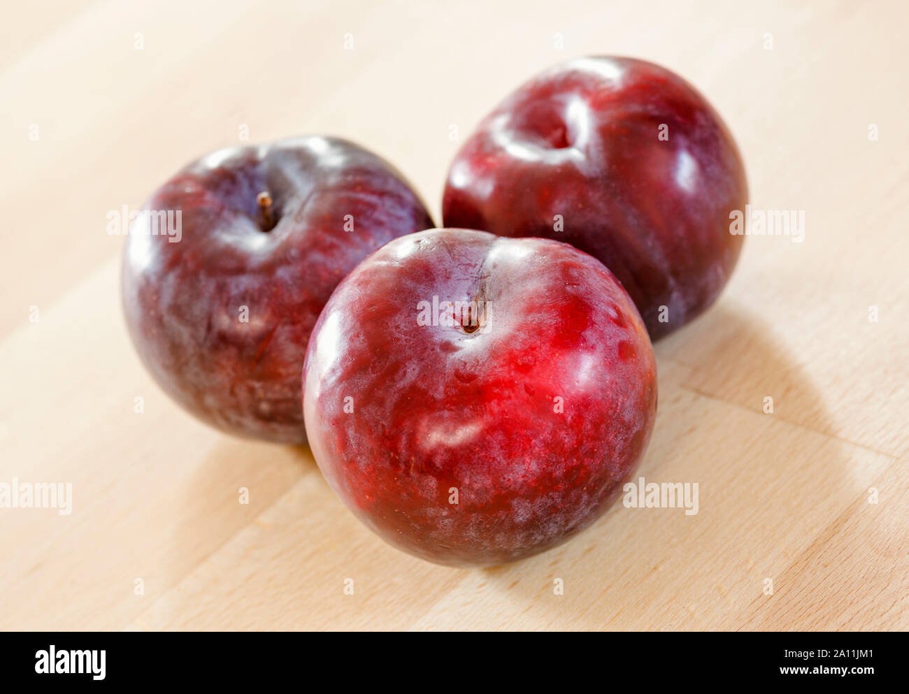 Three plums on a wooden surface Stock Photo