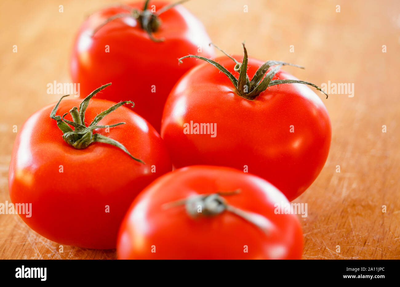Tomatoes on a wooden surface, close up Stock Photo