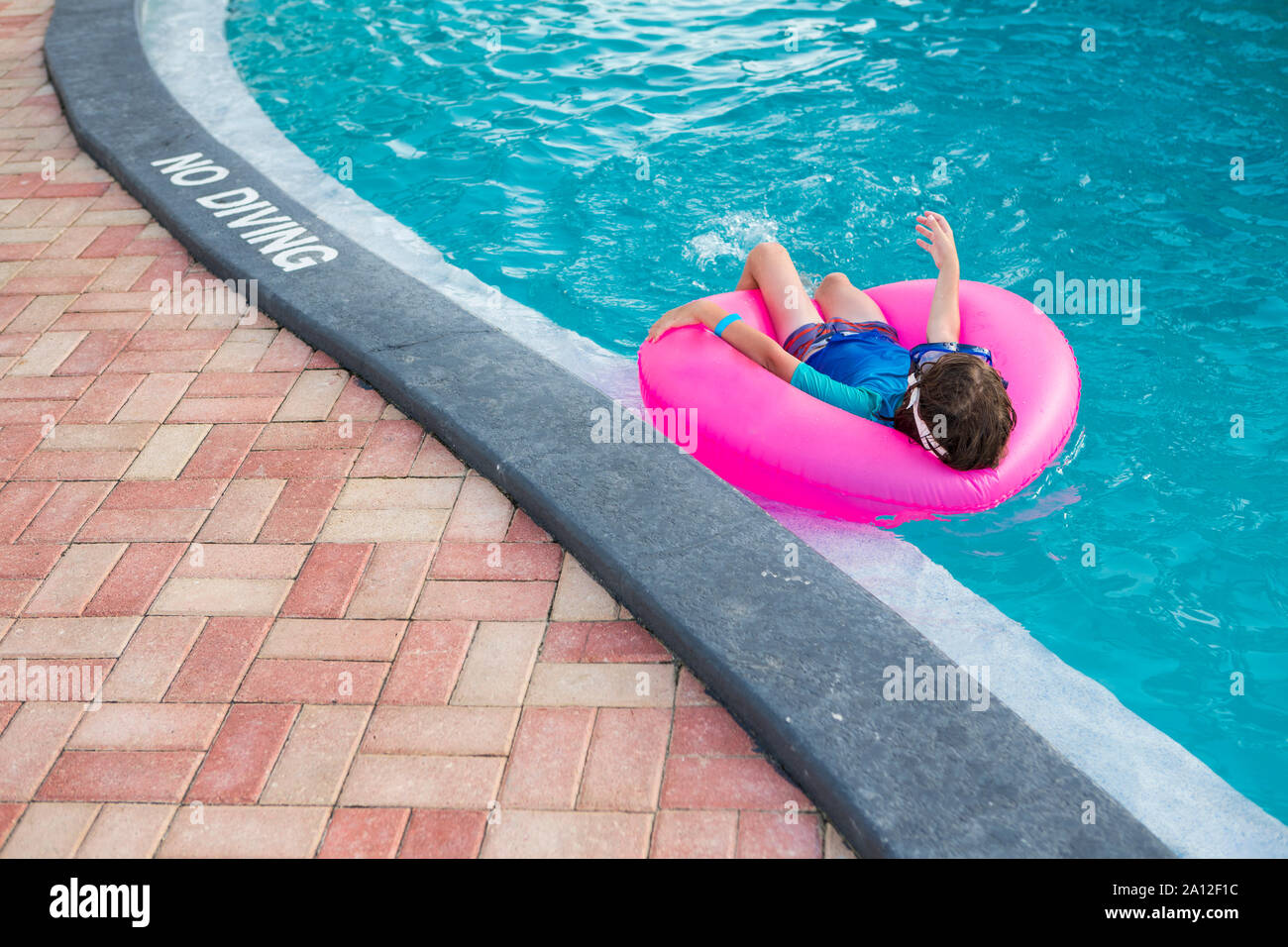 siblings playing in pool with colorful floaties. Stock Photo