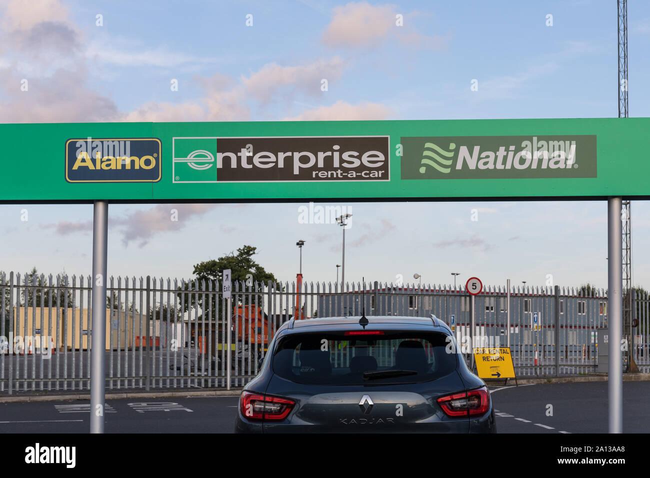 Alamo, Enterprise and National signs at a car rental depot - Manchester Airport Car Rental Village, UK Stock Photo