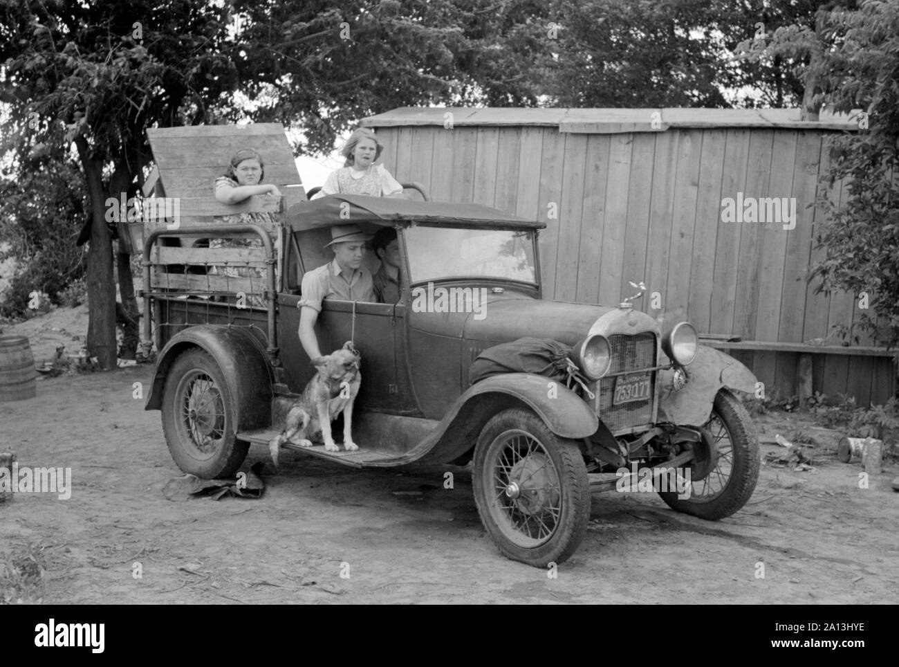 Great Depression era photograph of a migrant family in a packed car preparing to leave. Stock Photo