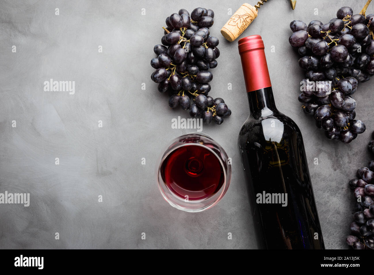 Red wine in a glass and ripe grapes on gray background, top view Stock Photo