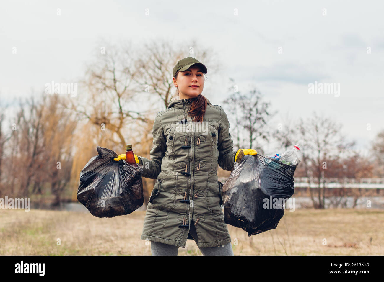 Litter picking. Woman volunteer cleaning up the trash in park. Picking up garbage outdoors. Ecology and environment concept. Saving planet Stock Photo
