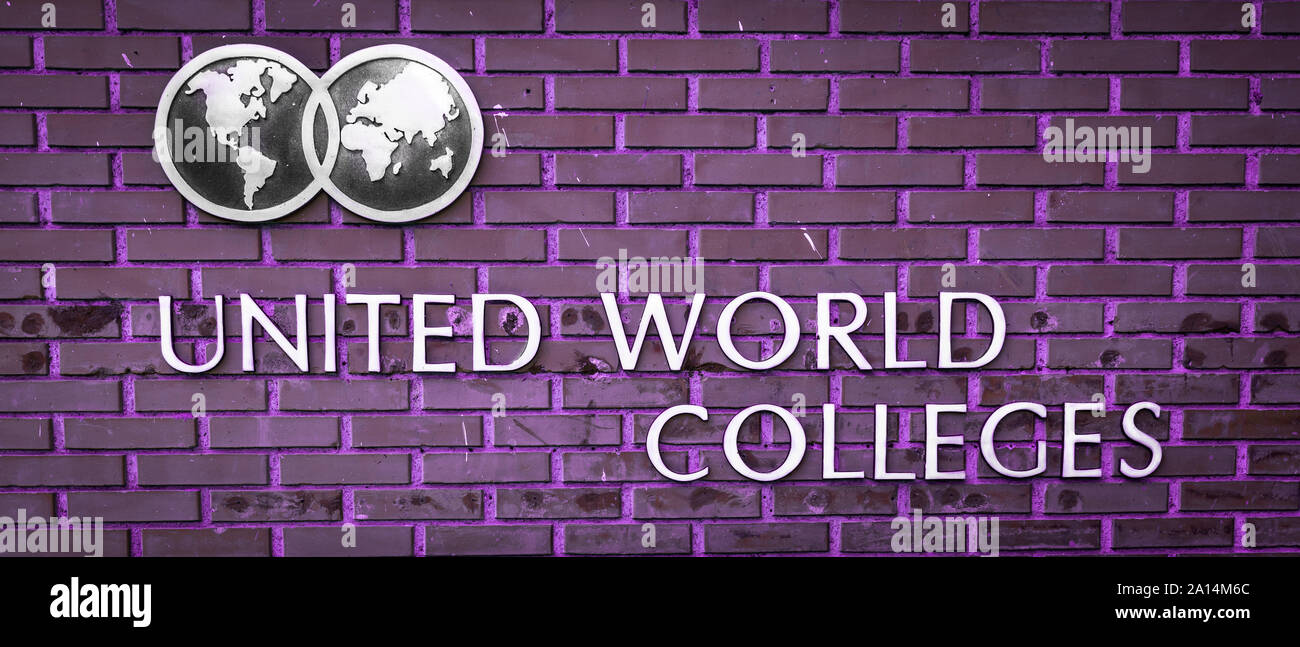 The Logo and name of the United World Colleges on the background of a violet brick wall Stock Photo