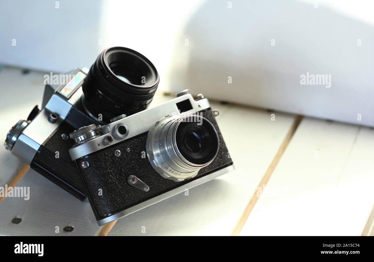 Two black old-school vintage film photo cameras on white wooden planks, sunlit interior Stock Photo