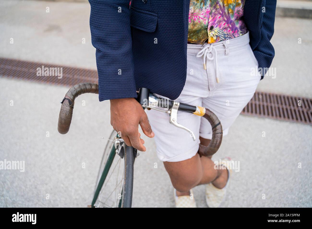 Close-up of stylish man leaning on bicycle Stock Photo