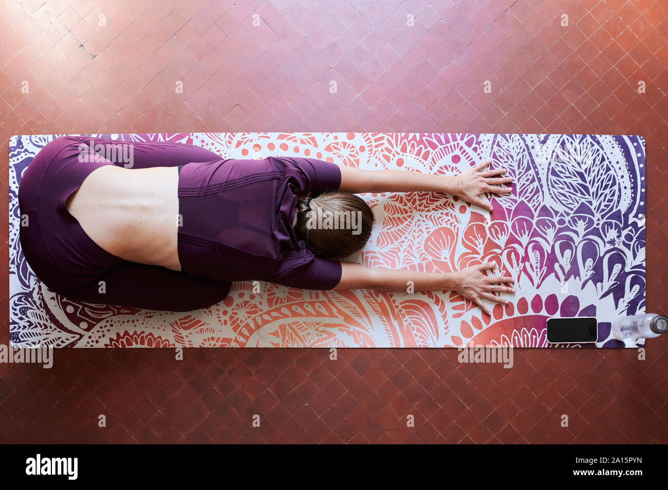 Young brunette woman practising yoga in student dorm, child position from above Stock Photo