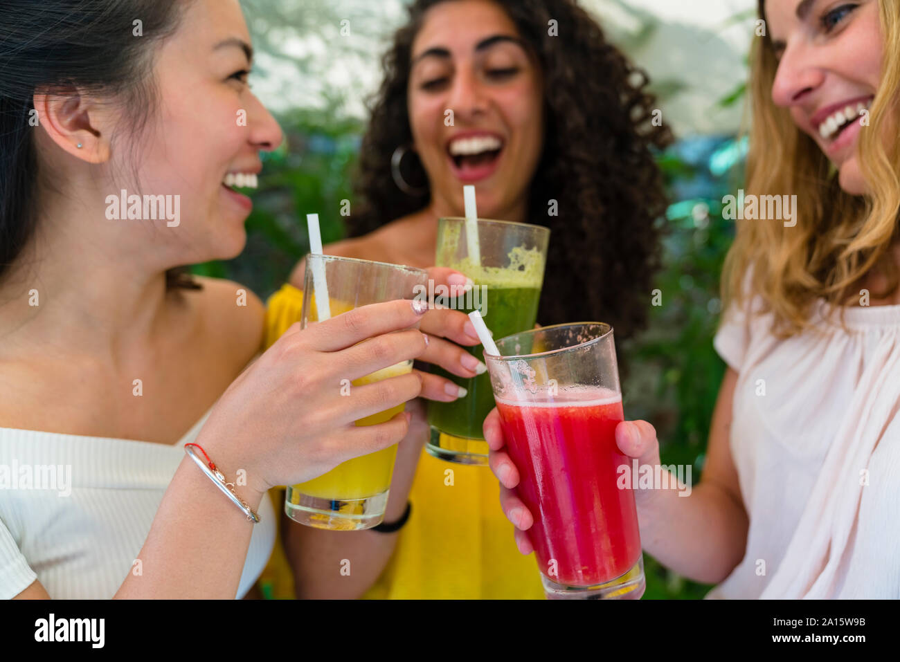 Three happy young women toasting with healthy drinks Stock Photo