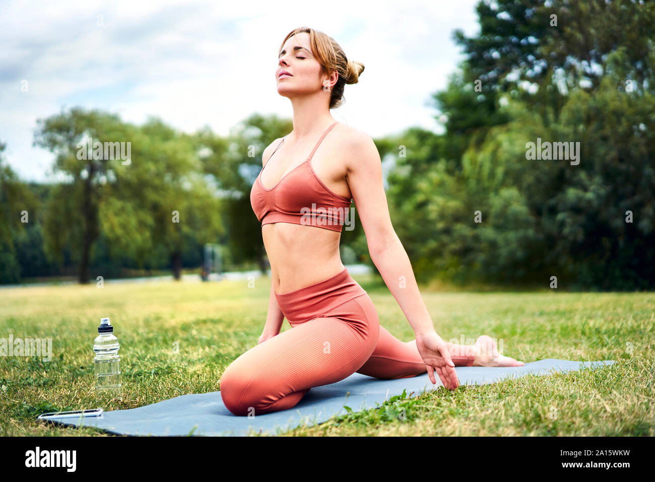 Woman practicing yoga in park Stock Photo