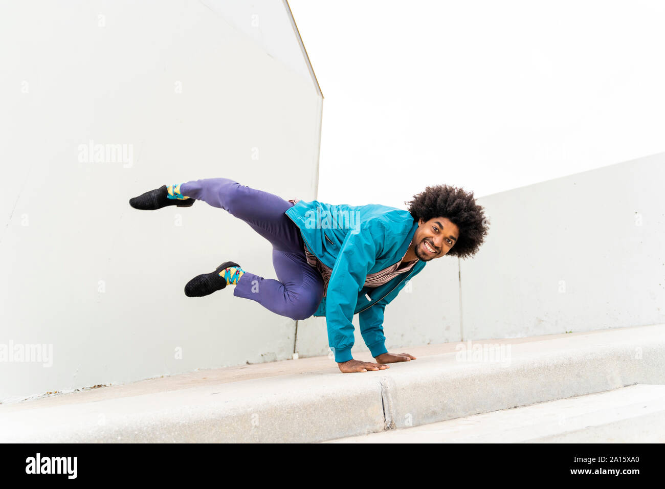 Young hipster man dancing, white wall in the background Stock Photo