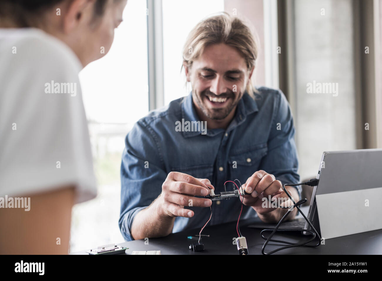 Smiling young man and woman working on computer equipment in office Stock Photo
