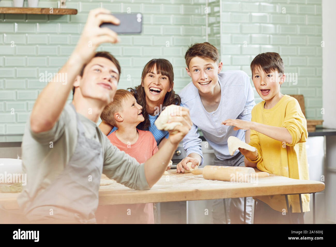 Sone taking pictures of his mother and brothers, preparing pizza at home Stock Photo