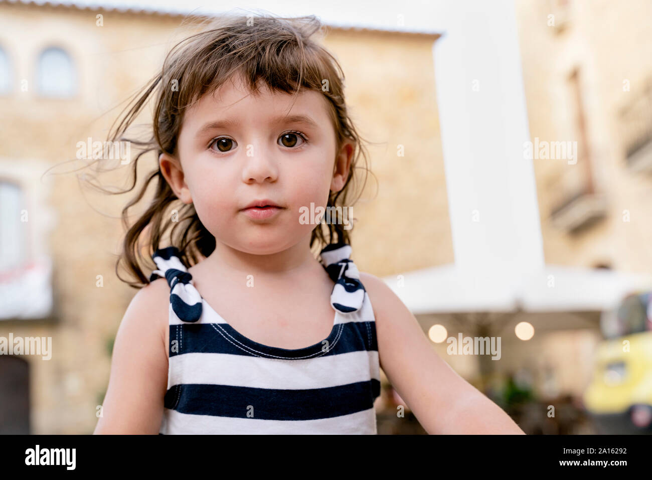 Portrait of cute little girl in summer wearing a striped dress Stock Photo