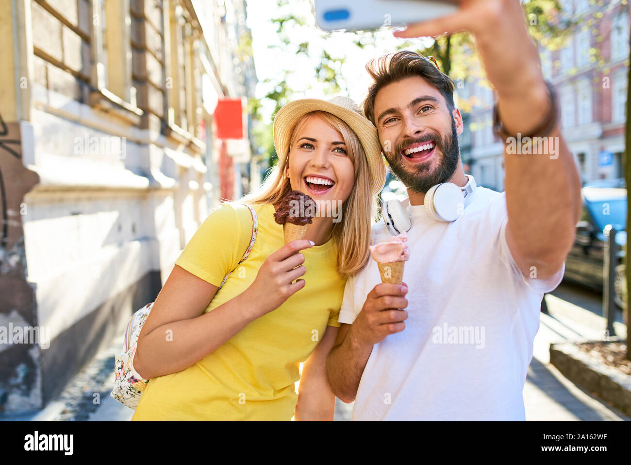 Happy young couple taking a selfie while eating ice cream in the city Stock Photo
