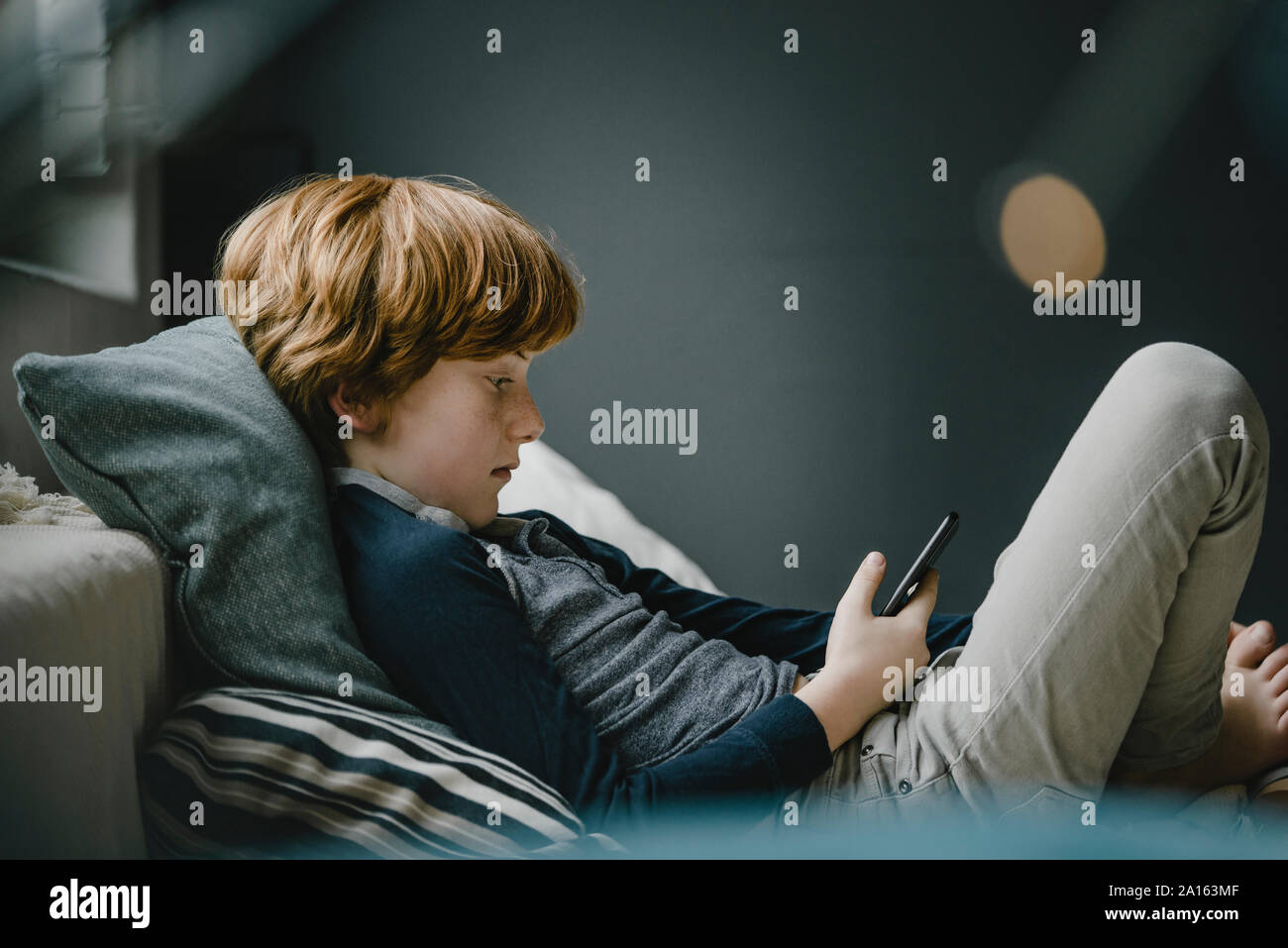 Redheaded boy lying on couch looking at cell phone Stock Photo