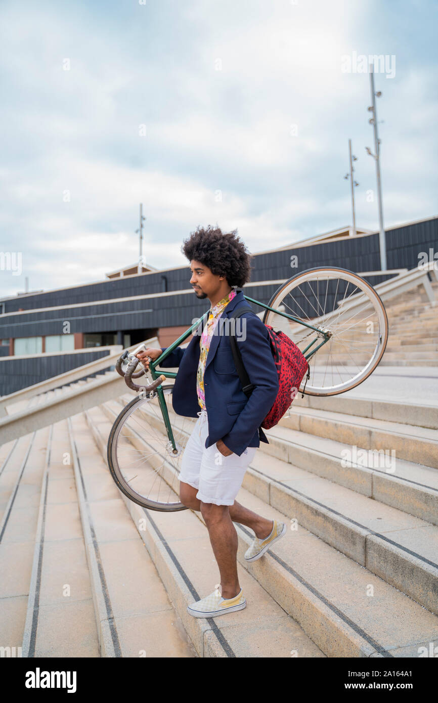 Stylish man carrying bicycle on stairs in the city Stock Photo