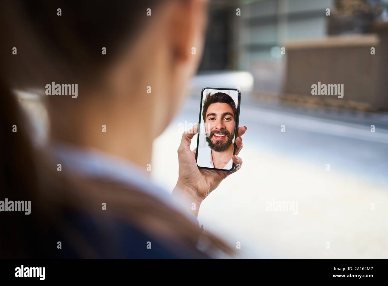 Close-up of businesswoman using smartphone chatting with colleague in factory Stock Photo