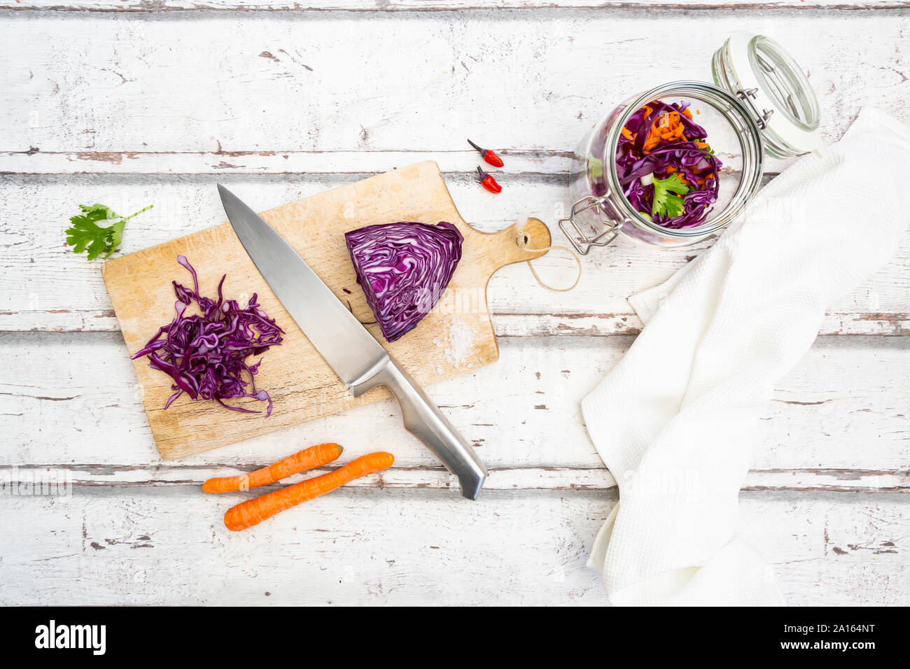 Red cabbage, chili peppers, carrots and coriander on wooden table Stock Photo