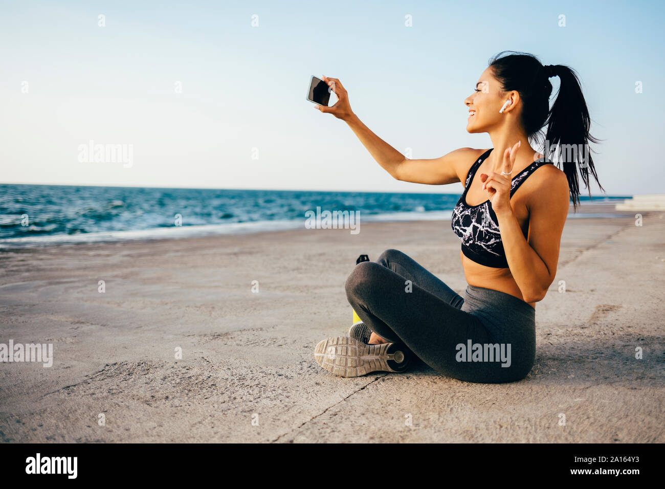 Woman using smartphone and taking a selfie, sitting on a pier Stock Photo
