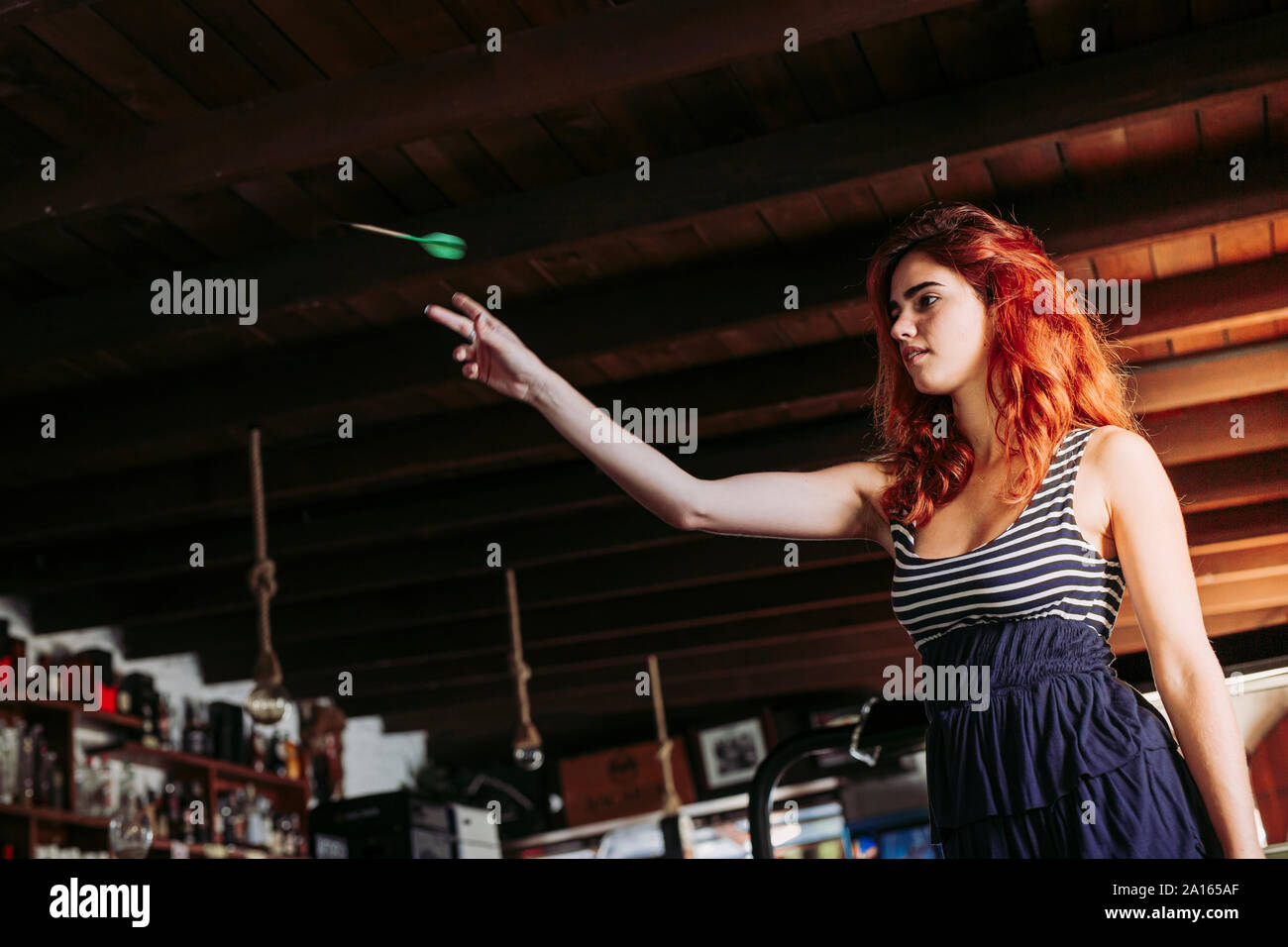 Young woman playing darts in a sports bar Stock Photo