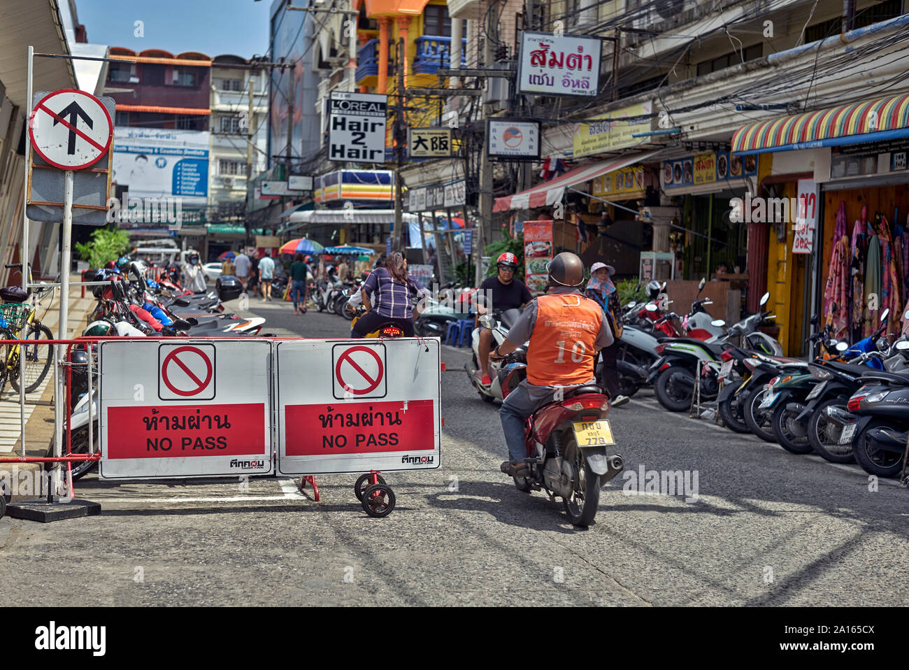 No entry sign. Motorbike riders blatantly ignoring a No Pass sign and heading the wrong way down a one way street. Thailand Southeast Asia Stock Photo
