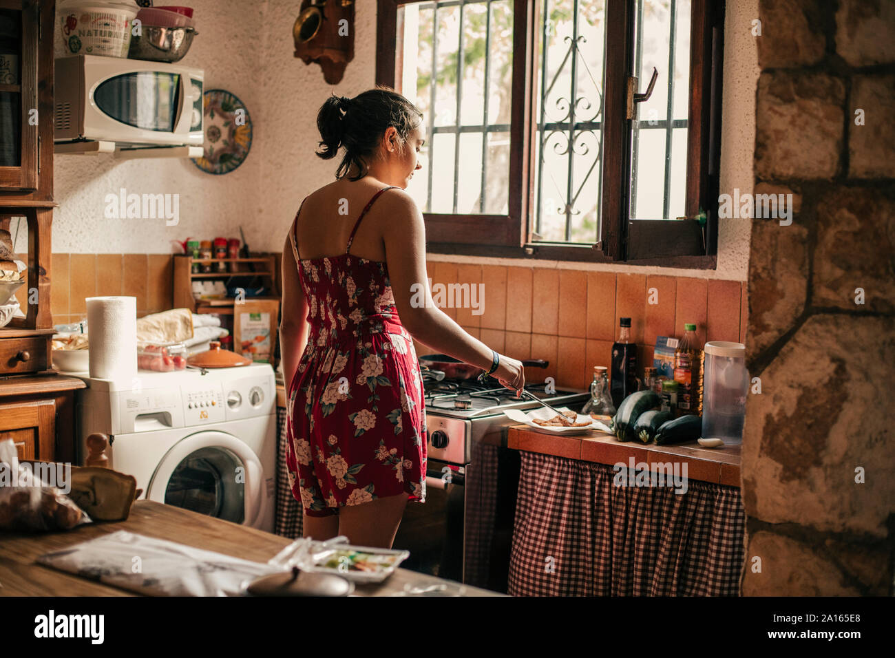 Rear view of woman cooking in kitchen Stock Photo