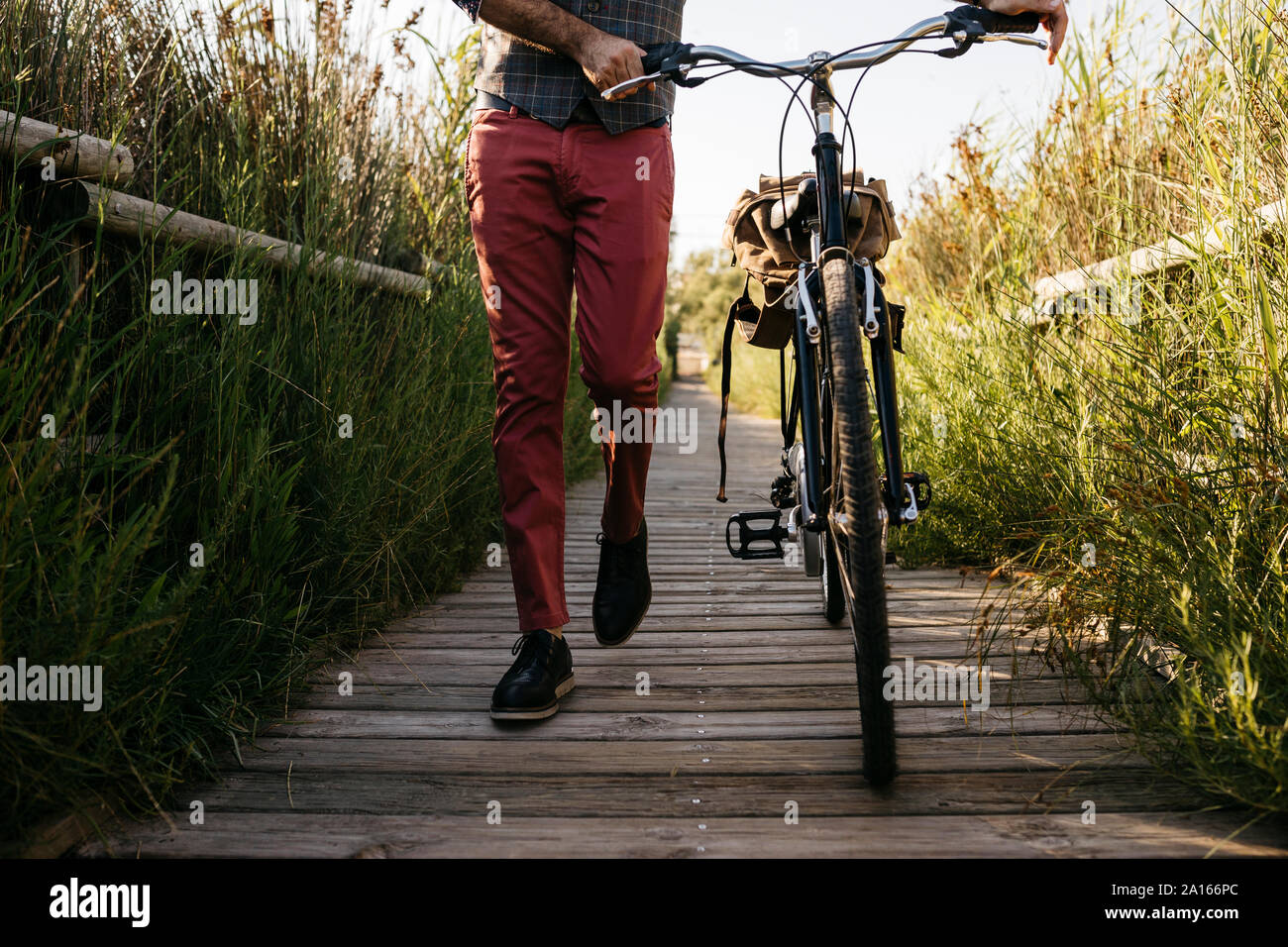 Well dressed man walking with his bike on a wooden walkway in the countryside after work Stock Photo
