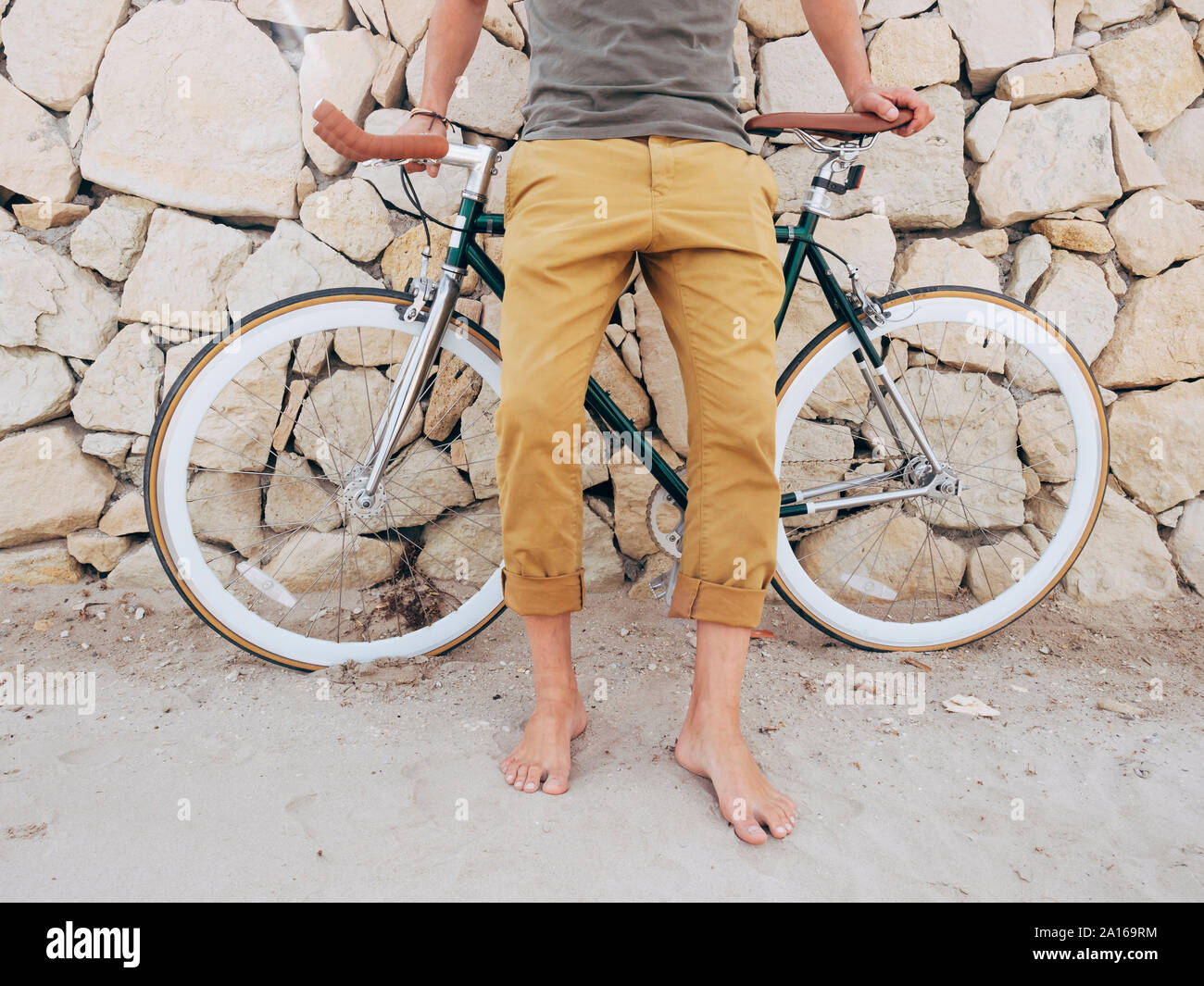 Barefoot man with Fixie bike in front of natural stone wall on the beach, partial view Stock Photo