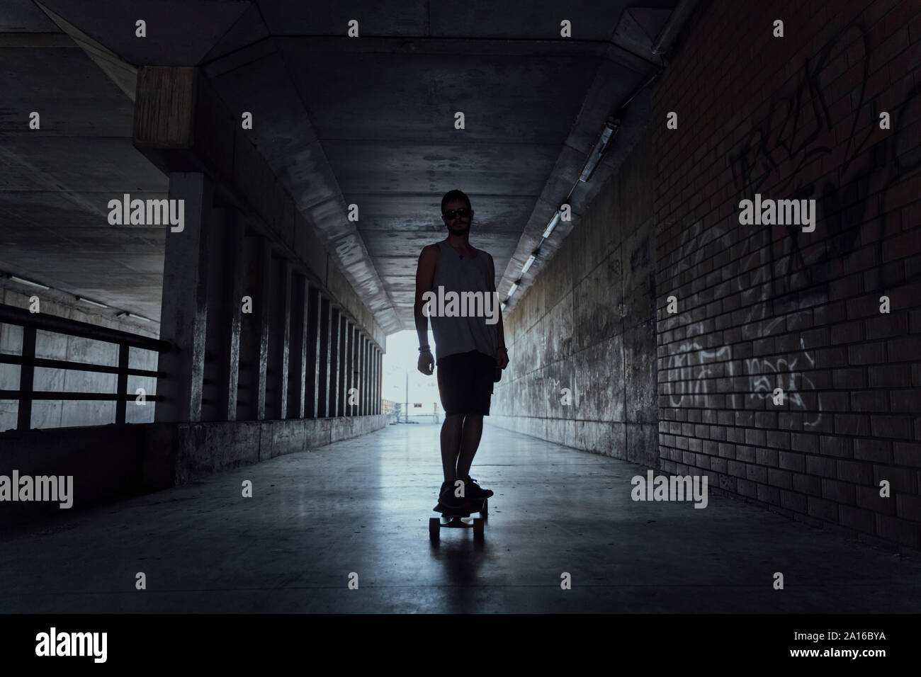 Young man with longboard in a tunnel Stock Photo