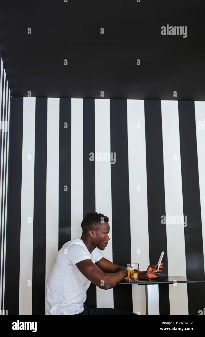 Young man sitting at table with a drink using cell phone Stock Photo