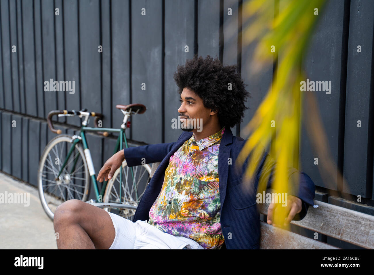 Stylish man with bicycle sitting on a bench Stock Photo