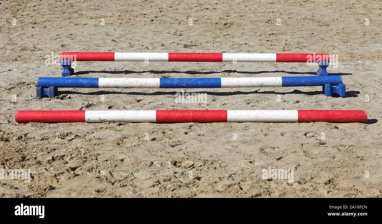 Colorful barriers on the ground for jumping horses and riders at riding school as a background.Obstacles for horses in a riding school Stock Photo