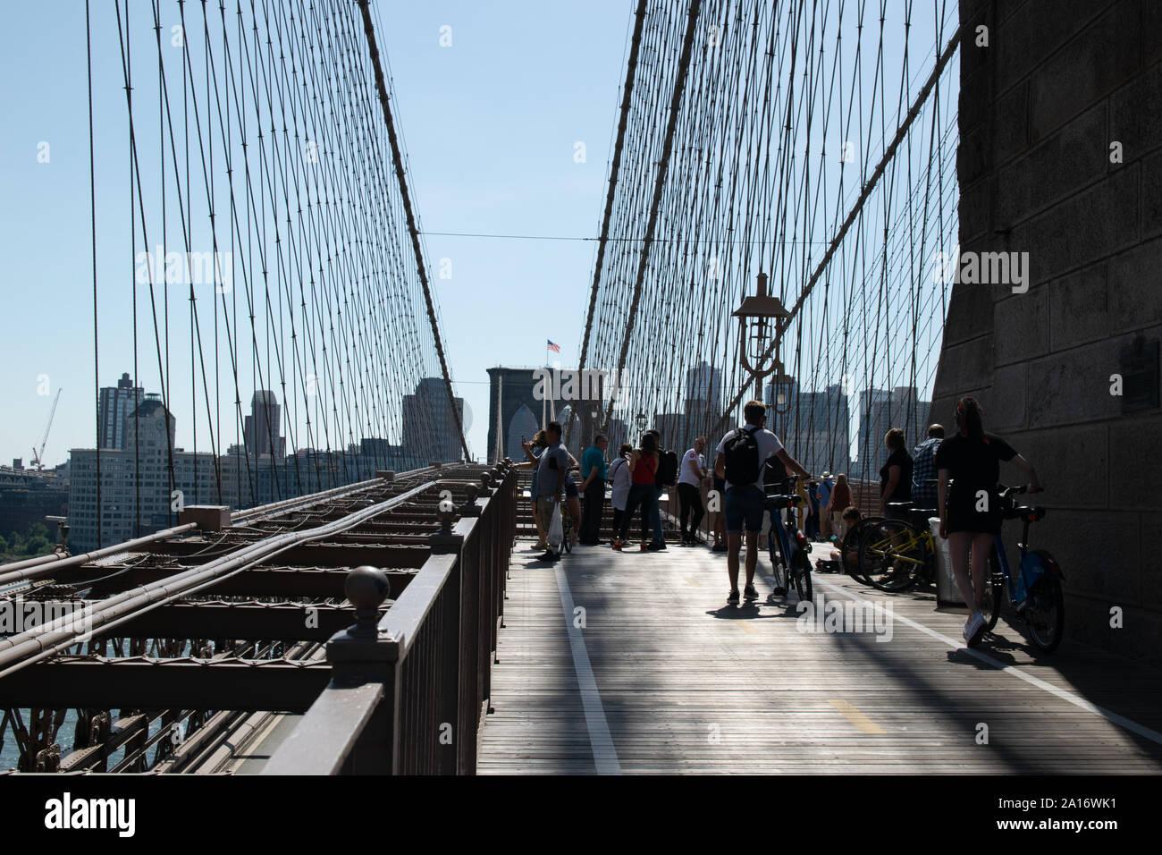 Fußgänger und Fahradfahrer teilen sich die obere Etage der Brooklyn Bridge Stock Photo