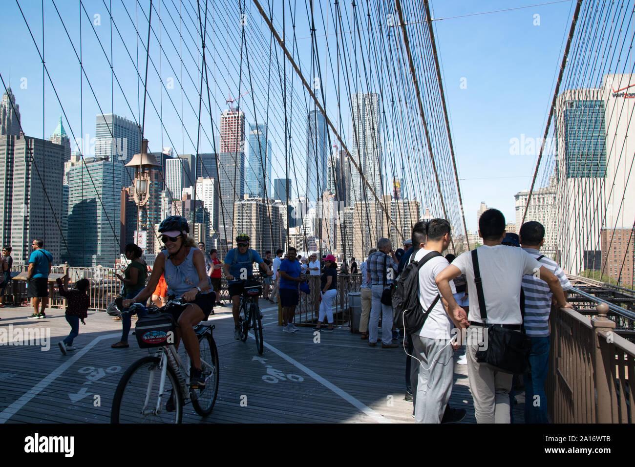 Fußgänger und Fahradfahrer teilen sich die obere Etage der Brooklyn Bridge. Touristen genießen den Blick auf Manhattan Stock Photo