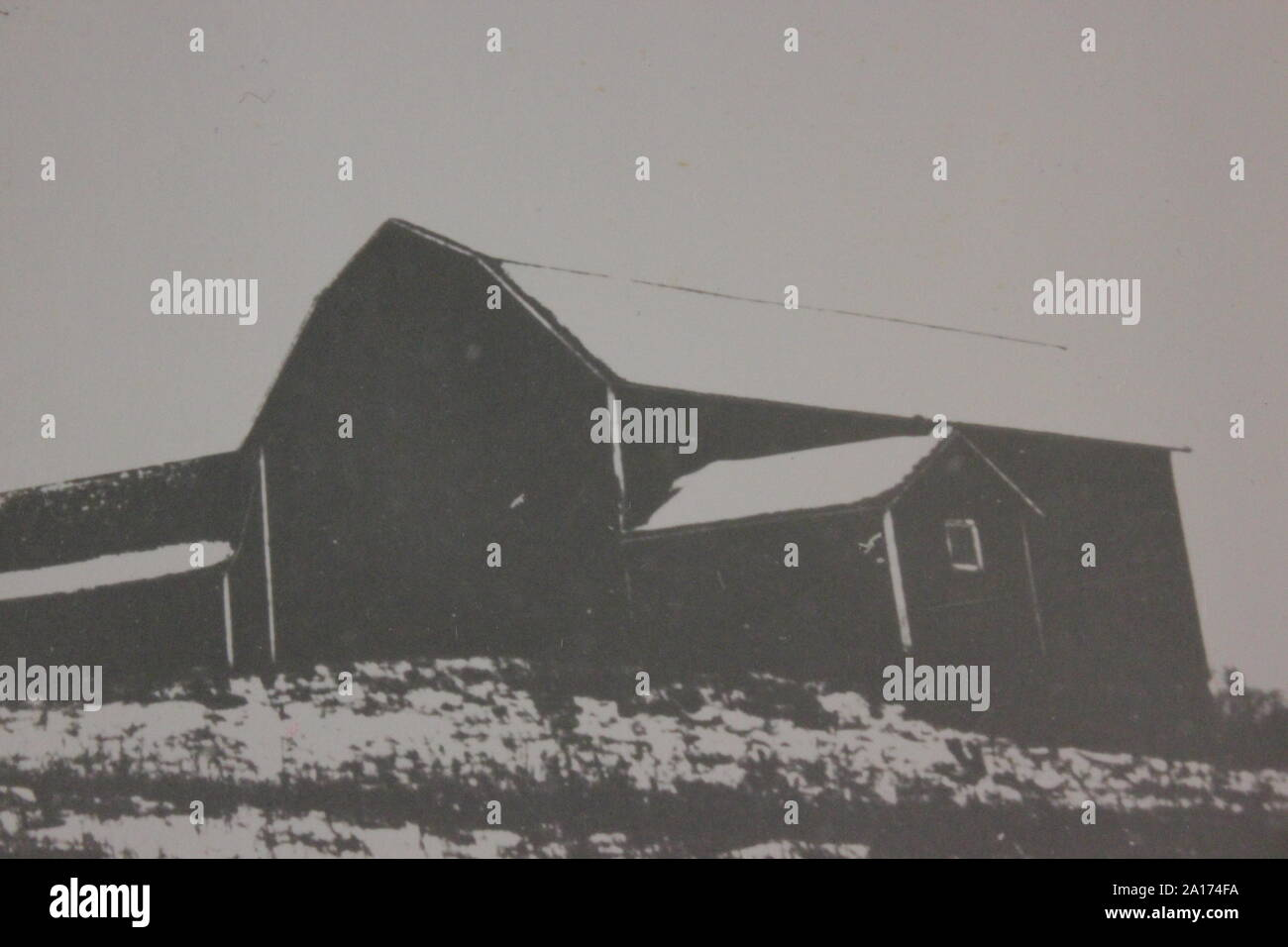 Fine black and white art photography from the 1970s of a barn sitting on top of a hill. Stock Photo