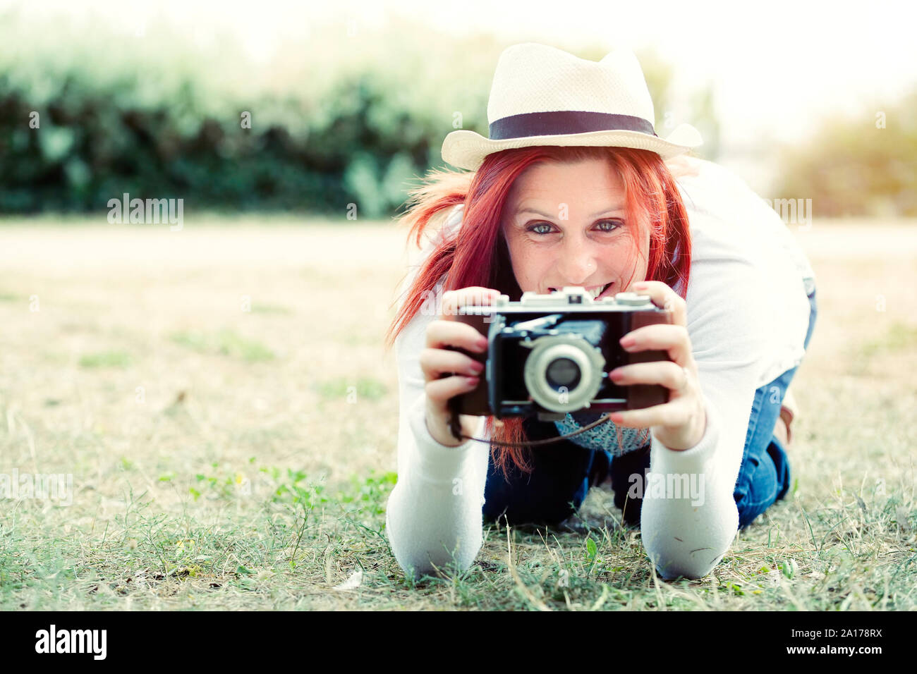 Portrait in the nature of a beautiful smiling red-haired woman using an old camera. vintage treatment Stock Photo